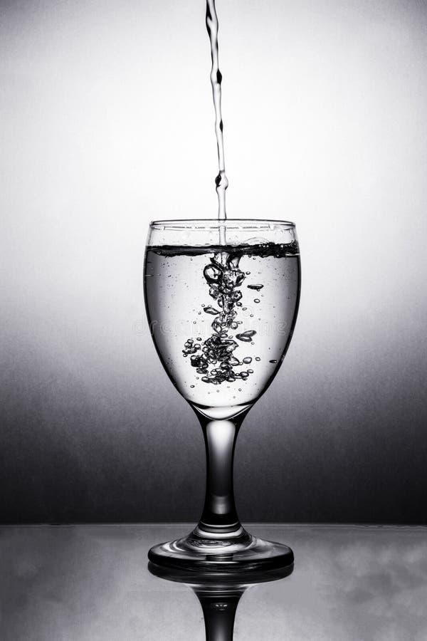 Agua en vidrio con el chapoteo del agua imagenes de archivo