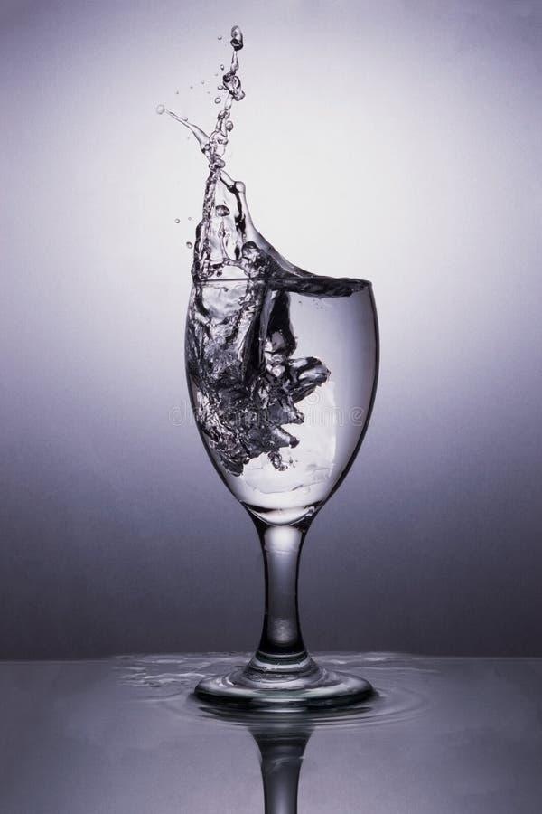 Agua en vidrio con el chapoteo del agua fotografía de archivo libre de regalías