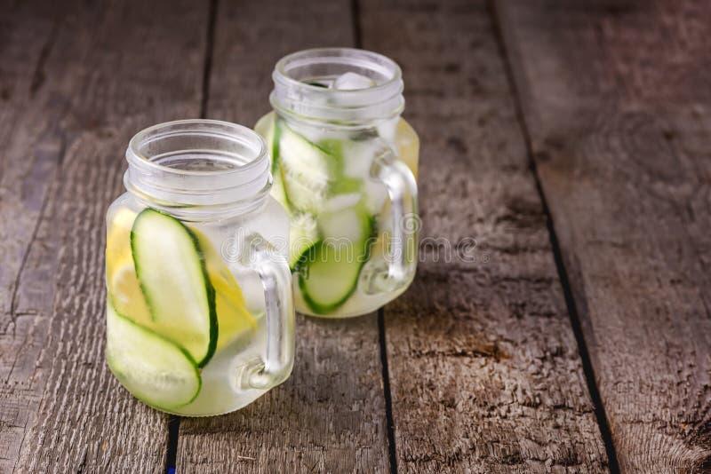 Agua fría fresca con el limón y agua sana infundida pepino del Detox del agua con el fondo de madera del limón y del pepino horiz fotografía de archivo