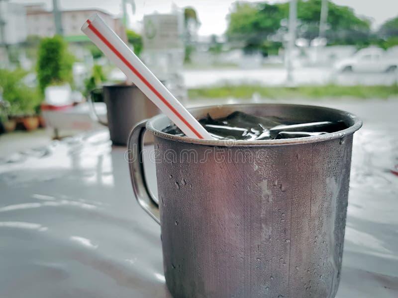 Agua helada fría en taza del acero inoxidable con la paja imagen de archivo libre de regalías