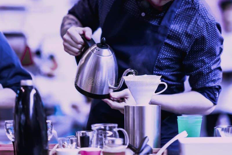 Agua hirvienda de colada del barista profesional de la caldera especial en el filtro, preparación del café del filtro color púrpu imágenes de archivo libres de regalías
