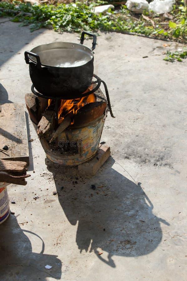 agua hirvienda del pote negro para cocinar en la estufa encendida al lado de f foto de archivo