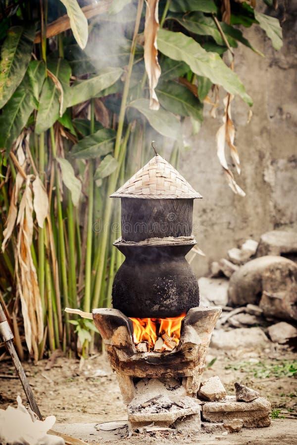 Agua hirvienda del pote para cocinar el arroz pegajoso imagenes de archivo