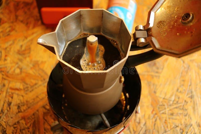 Agua hirvienda que corre a través del café molido en un tamiz más bajo que crea un tiro del café express aromático en el pote imagenes de archivo