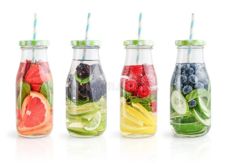 Agua infundida con las frutas frescas, las verduras y la baya en botellas fotografía de archivo