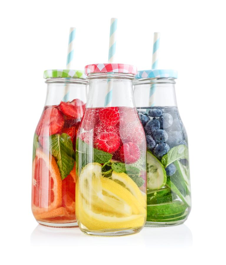 Agua infundida con las frutas frescas, las verduras y la baya en botellas imagenes de archivo