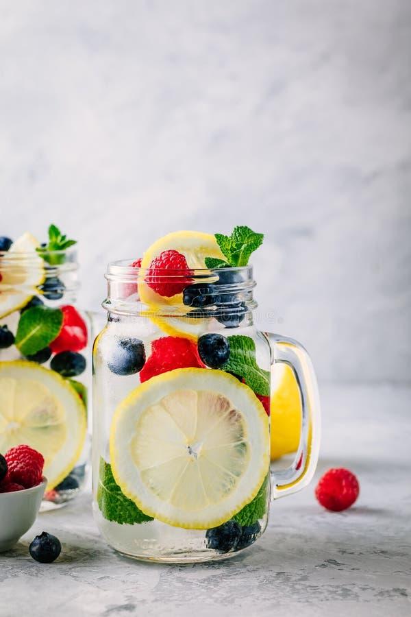 Agua infundida del detox con la rebanada, la frambuesa, el arándano y la menta del limón Cóctel o limonada helado del verano en t fotografía de archivo