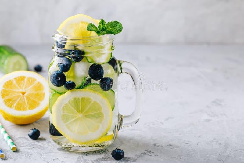 Agua infundida del detox con las rebanadas del limón y del pepino, el arándano y la menta Limonada helada del verano en el tarro  imágenes de archivo libres de regalías