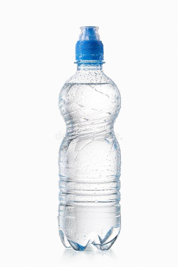 Agua La pequeña botella de agua plástica con agua cae en blanco detrás imagen de archivo libre de regalías