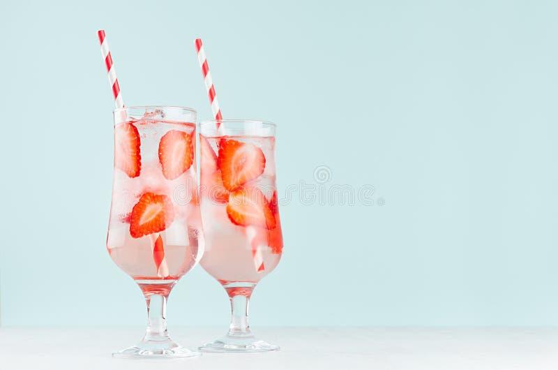 Agua mineral de la fresa fresca de la aptitud con las rebanadas maduras de la fresa, cubos de hielo, paja, tónico en vidrio elega imagen de archivo libre de regalías