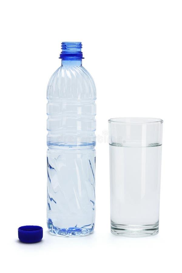 Agua mineral en un vidrio y una botella imágenes de archivo libres de regalías