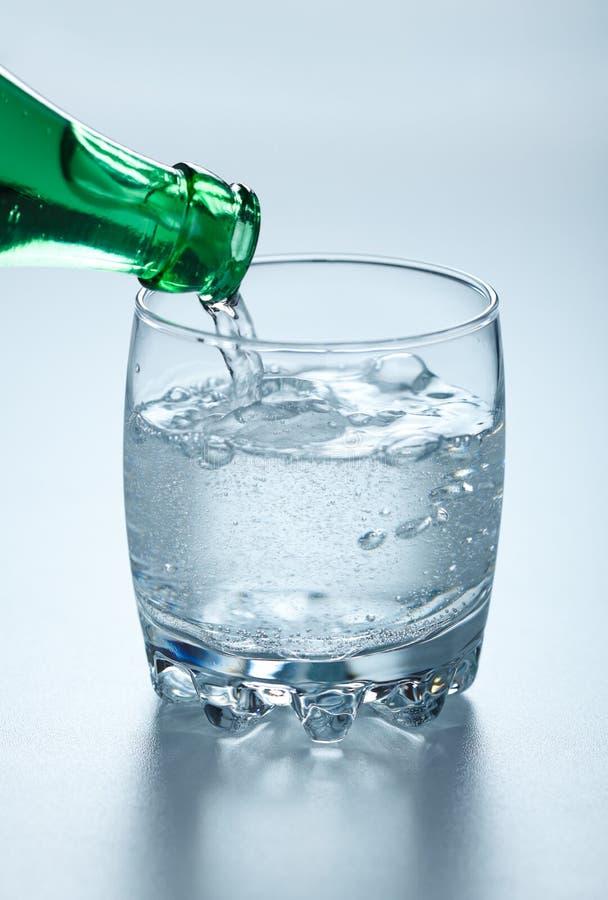 Agua mineral que vierte en el vidrio imágenes de archivo libres de regalías