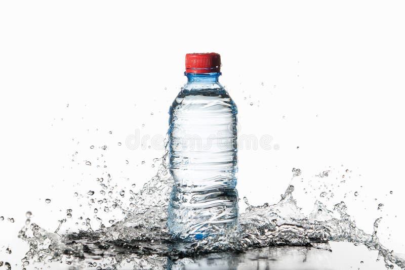 Agua Pequeña botella de agua plástica con descensos y chapoteo del agua encendido imagenes de archivo