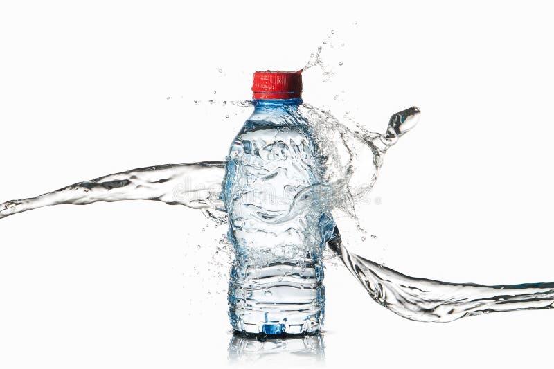 Agua Pequeña botella de agua plástica con descensos y chapoteo del agua encendido imagen de archivo libre de regalías