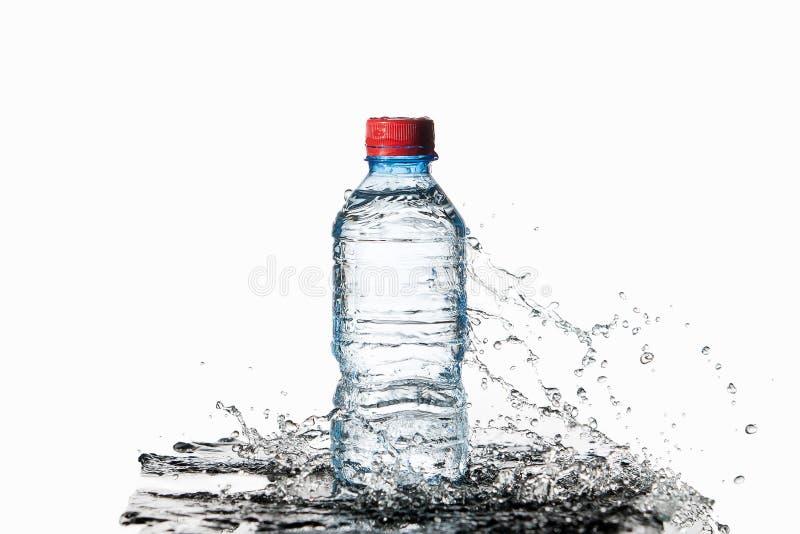 Agua Pequeña botella de agua plástica con descensos y chapoteo del agua encendido imágenes de archivo libres de regalías