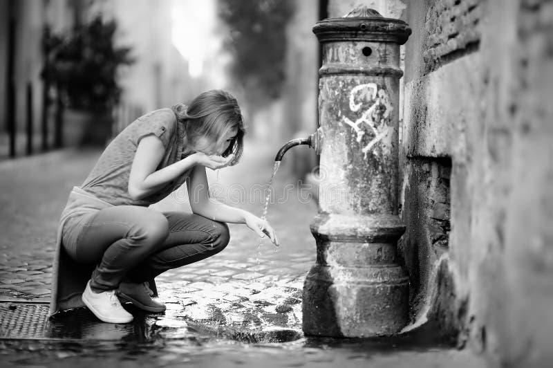 Agua potável bebendo da jovem mulher da fonte em Roma, Itália fotos de stock