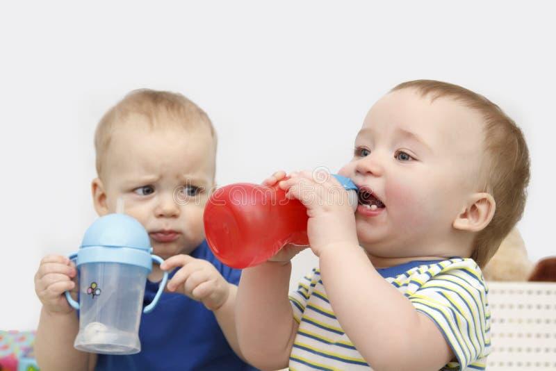 Agua potable de dos niños pequeños fotos de archivo
