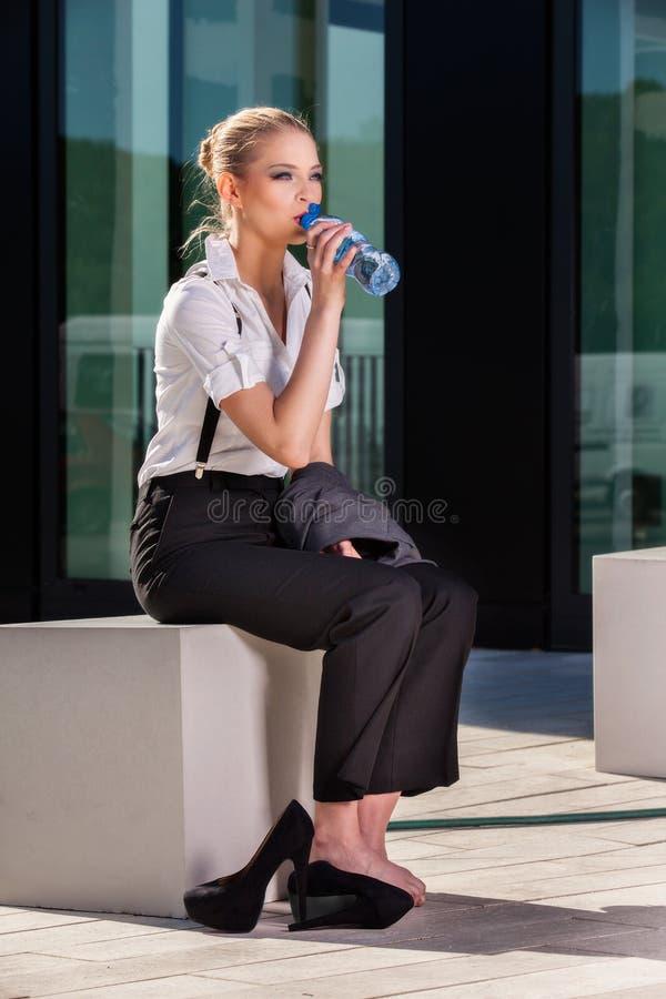 Agua potable de la empresaria de una pequeña botella imagen de archivo libre de regalías