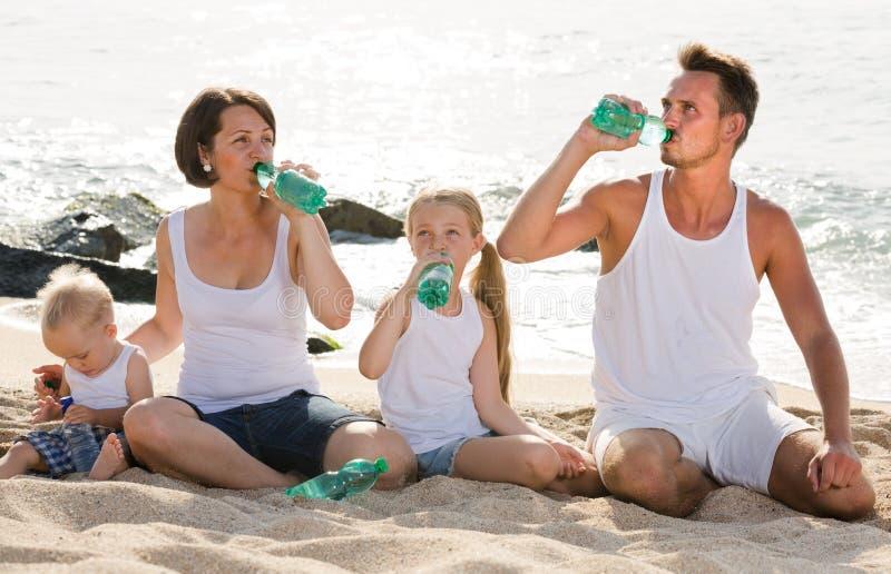Agua potable de la familia en la playa fotografía de archivo libre de regalías