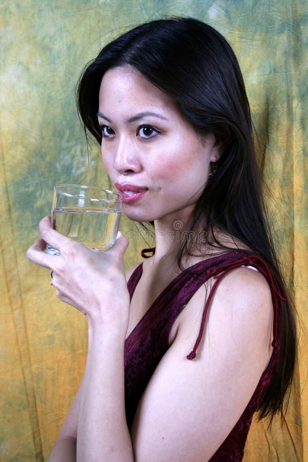 Agua potable de la muchacha asiática fotos de archivo libres de regalías
