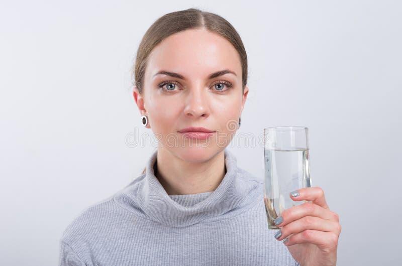 Agua potable de la muchacha atractiva en fondo ligero fotos de archivo libres de regalías