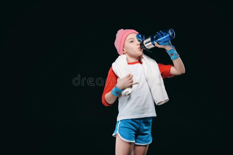 Agua potable de la muchacha deportiva linda de la botella fotos de archivo