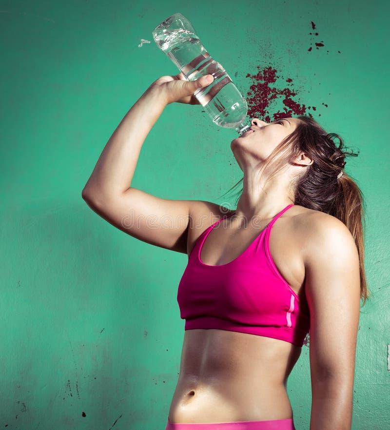 Agua potable de la muchacha después de entrenar fotos de archivo