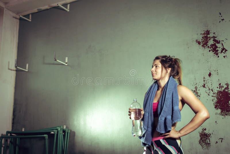 Agua potable de la muchacha después de entrenar imagenes de archivo