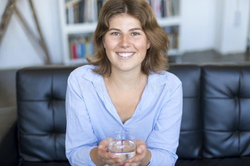 Agua potable de la muchacha que se sienta en un sofá en casa y que mira el Ca fotografía de archivo