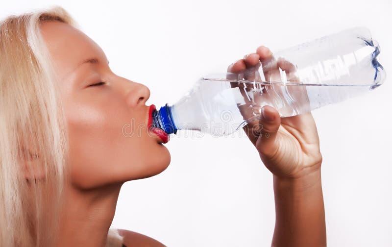 Agua potable de la muchacha rubia joven atractiva foto de archivo
