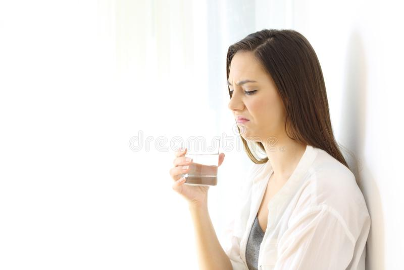 Agua potable de la mujer asqueada con mún gusto en blanco imagen de archivo libre de regalías