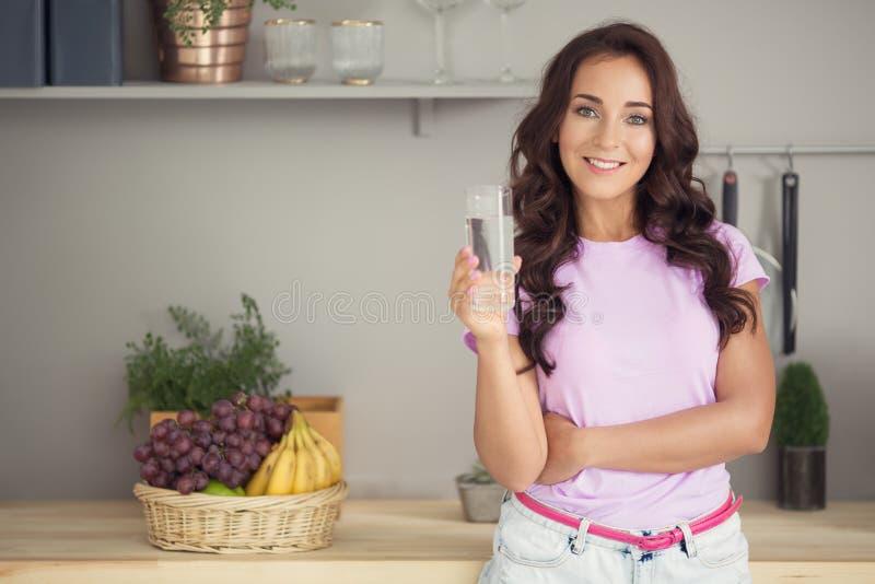 Agua potable de la mujer atractiva joven en cocina imagenes de archivo