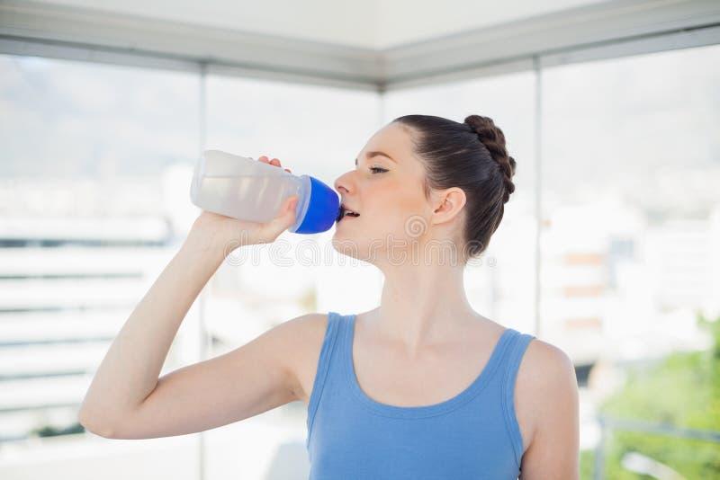 Agua potable de la mujer bonita del ajuste en su frasco plástico imagen de archivo