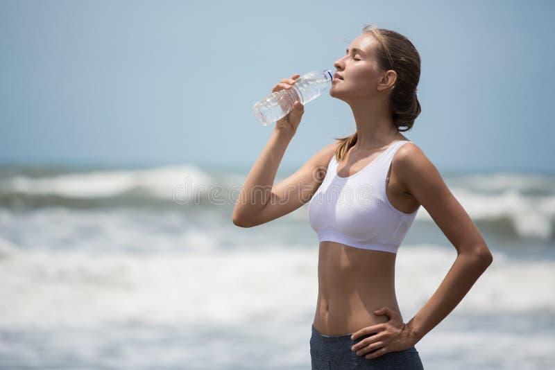 Agua potable de la mujer delgada joven después de entrenar en la playa fotografía de archivo libre de regalías
