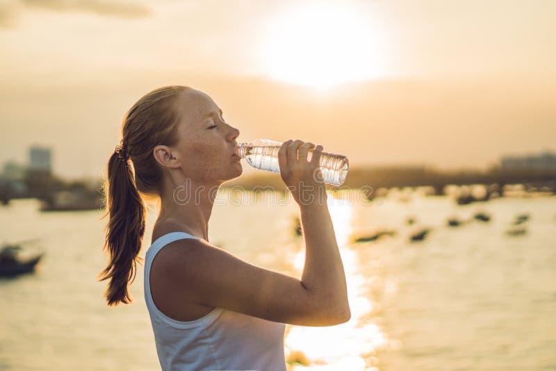 Agua potable de la mujer deportiva al aire libre el día soleado foto de archivo