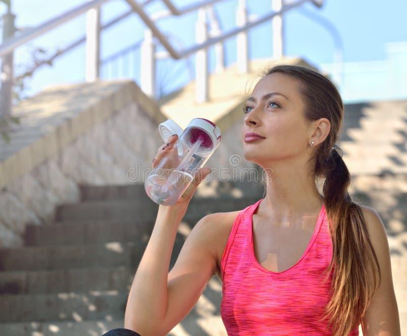 Agua potable de la mujer deportiva al aire libre el día soleado imagenes de archivo