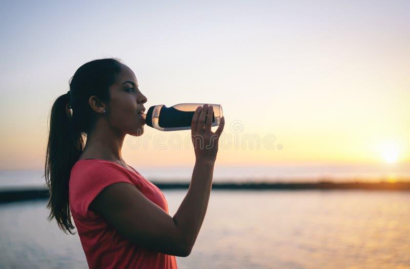 Agua potable de la mujer deportiva joven mientras que teniendo una rotura - muchacha de la salud que descansa en la puesta del so imagenes de archivo