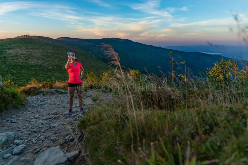 Agua potable de la mujer durante el funcionamiento en montañas en el verano fotos de archivo libres de regalías