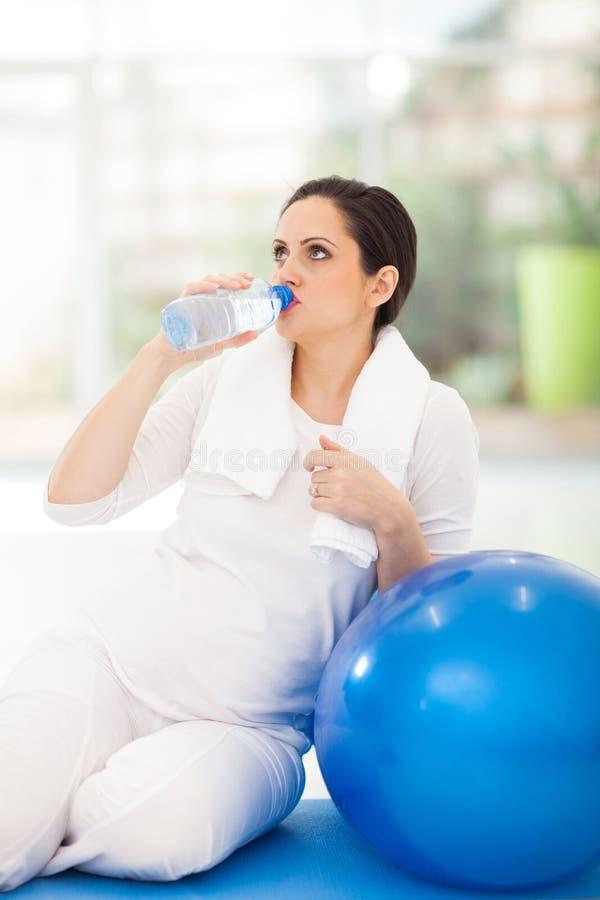 Agua potable de la mujer embarazada fotos de archivo libres de regalías