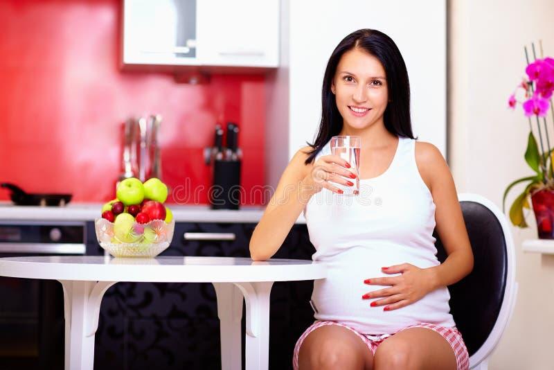 Agua potable de la mujer embarazada en cocina imagen de archivo libre de regalías