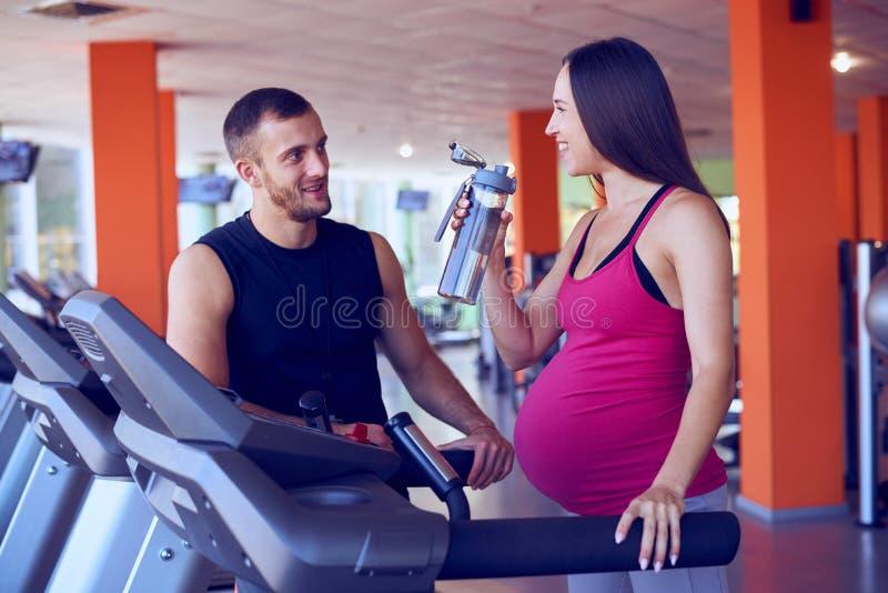 Agua potable de la mujer embarazada mientras que habla al instructor personal foto de archivo libre de regalías
