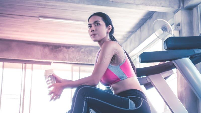 Agua potable de la mujer en entrenamiento de la rueda de ardilla en gimnasio de la aptitud imagenes de archivo