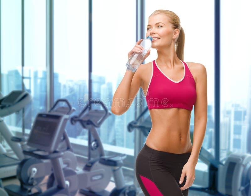 Agua potable de la mujer feliz de la botella en gimnasio imagen de archivo libre de regalías