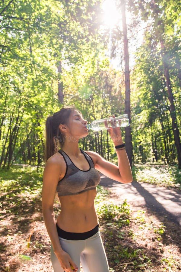 Agua potable de la mujer hermosa de la aptitud y el sudar después de ejercitar en día caliente del verano en parque Atleta de sex fotos de archivo