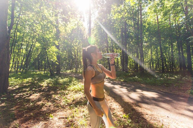Agua potable de la mujer hermosa de la aptitud y el sudar después de ejercitar en día caliente del verano en parque Atleta de sex fotos de archivo libres de regalías