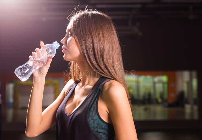 Agua potable de la mujer joven de la aptitud de la botella Hembra joven muscular en el gimnasio que toma una rotura del entrenami imágenes de archivo libres de regalías