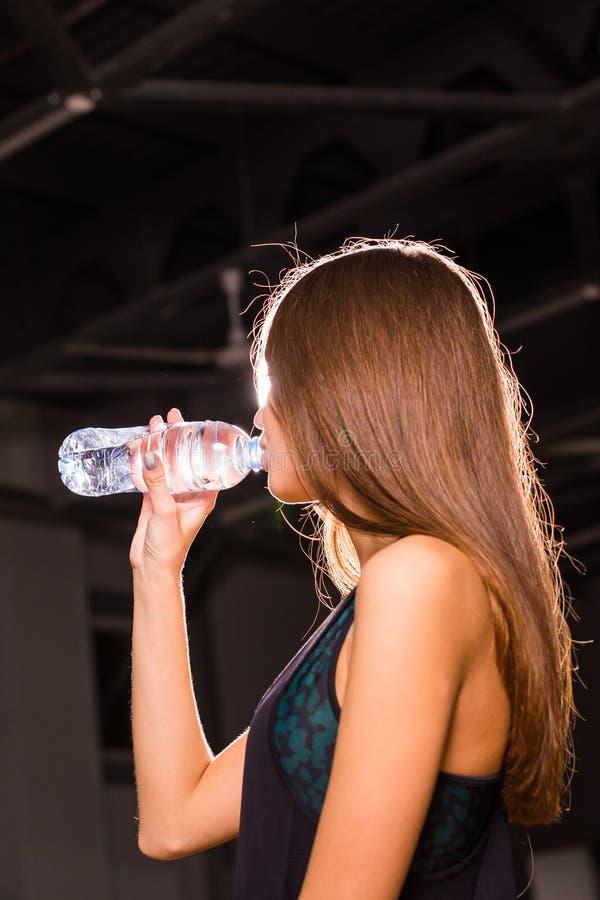 Agua potable de la mujer joven de la aptitud de la botella Hembra joven muscular en el gimnasio que toma una rotura del entrenami foto de archivo libre de regalías