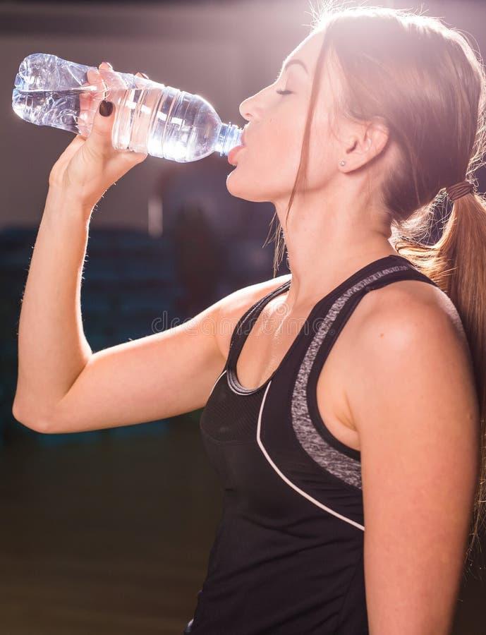 Agua potable de la mujer joven de la aptitud de la botella Hembra joven muscular en el gimnasio que toma una rotura del entrenami fotografía de archivo