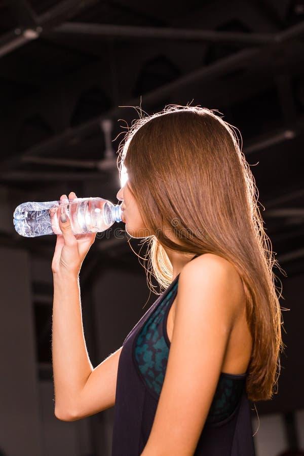 Agua potable de la mujer joven de la aptitud en el gimnasio Mujer muscular que toma la rotura después de ejercicio imagen de archivo