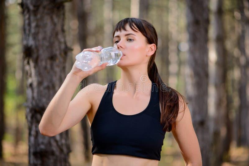 Agua potable de la mujer joven del deporte durante el funcionamiento en el pino salvaje hermoso Forest Active Lifestyle Concept imagen de archivo libre de regalías